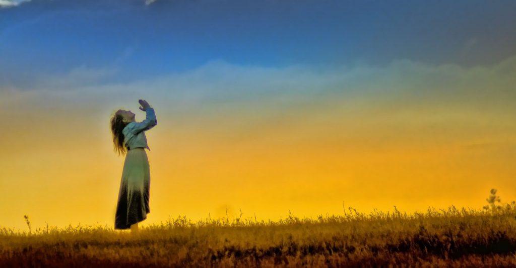 woman prays in a field, prayer, detachment